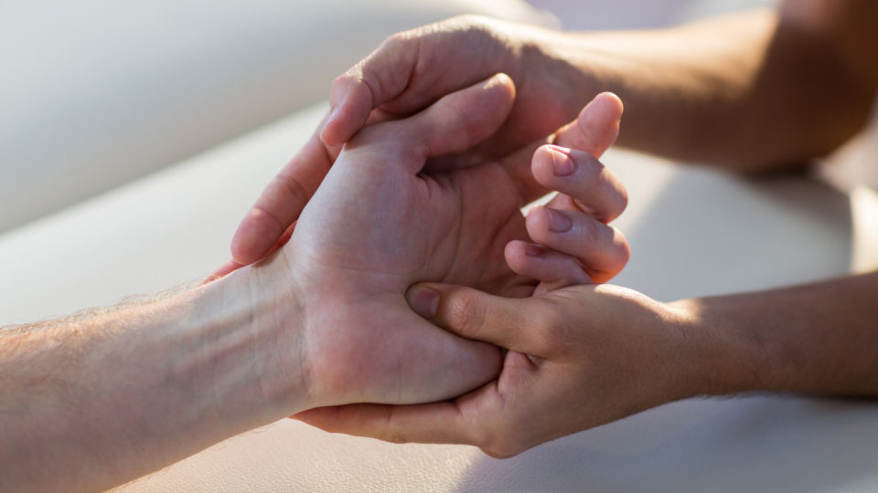 Close-up of physiotherapist giving hand massage to patient in clinic